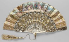 1850, Spain - Fan - Obverse: figures looking at painting. Reverse: figures in pastoral setting. Gilt and painted floral scrollwork at sides and borders, narrow gilt band at borders. Carved mother-of-pearl sticks heavily ornamented with gilt-silver and copper, gold foil backing on guards. Diamond paste studs in rivet. White silk tassel embroidered with gilt-silver yarns and lavendar beads depends from stylized gilt ring ornamented with six topazes.