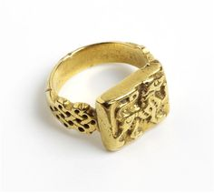 Ring, gold, cast and chased. The shaped shoulders of the decorated with an interlace pattern. The flat rectangular bezel set with a high relief lion passant, with incised detailing. Sicily, 12th century