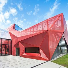 Faceted red metal creates sculptural facade for music centre...