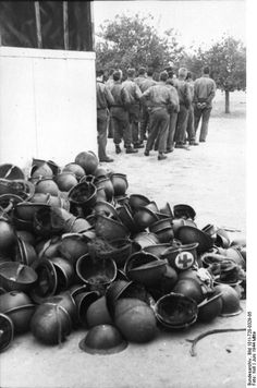Normandy, June 1944: Pile of US and British helmets belonging to the group of POWs standing in front of the building. These trophies invariably went back to the steel factory to add supplies desperately needed by the German armed forces. #WWII #War