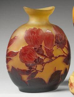 Émile GALLÉ (1846-1904), Grand vase gourde à panse aplatie, à col resserré et à ouverture en navette. Epreuve en verre multicouche bordeaux et rouge-rosé sur fond jaune-orangé. Décor de fleurs de magnolia en camée dégagé à l'acide. Signé.