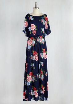 As ethereal as the cherry blossoms blooming around you, this navy blue maxi dress embodies your grace and grandeur. Made of an airy, woven fabric, and finessed with red, pink, and sky blue flowers, dramatic flutter sleeves, and an off-centered vent on its skirt, this frock is a divine example of your beguiling style.