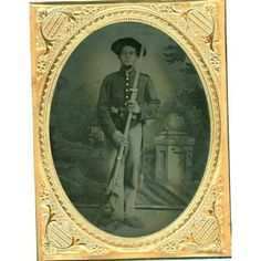 DOUBLE ARMED INDIANA SOLDIER, 1/4 plate tintype in dull leather case. Standing pose of John A. Brownlee, Company F, 58th Indiana standing with a wide brimmed hat, holds musket with bayonet and revolver tucked into his belt. Enlisted November 12th, 1861 and was discharged November 12th, 1864 serving his full three year enlistment. The unit fought at Shiloh, Corinth, Stones River, Chattanooga, Missionary Ridge, and during the entire Atlanta Campaign with Sherman through to Savannah.