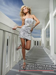 Strapless short patterned sequin sheath features wide beaded waistband with jeweled accents. Removable straps included.
