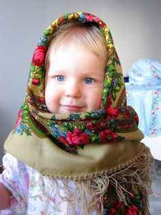 Kid in Russian clothes. Blue-eyed girl in Russian traditional shawl.