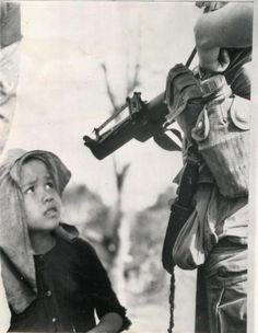 Vietnamese boy looks at M-79 grenade launcher held by U.S. soldier. 1968