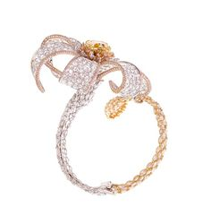 A 3-dimensional diamond bangle from Forms designed as sparkling as blossom, set with a yellow radiant cut diamond pistil, surrounded by pink, rose cut, and marquise diamond petals.