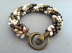 This bracelet is made with Gold, Copper, Cream, and Matte Bronze Iris Magatama beads. MEMBER - Creations Made By Lola