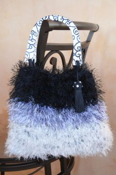 """The inspiration for this purse was the fun of the yarn. I love the look of the fancy new yarns.  Color: Black, White, and Gray  Material: Yarn. Snap closure.  Size: 10 1/2"""""""" high X 12"""" wide at the bottom and 9 1/2"""" at the top  Lining: Black satin. With one large pocket  HANDLE: Beautiful designer black and white plastic handle  Thank you for looking!"""