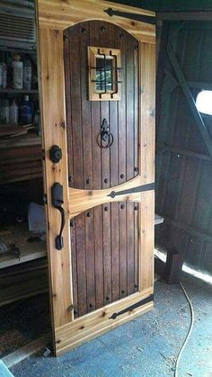 Rustic wood door with rivets. Middle cross member can be straight small window with bars is awesome.  I can decide to stain inlays darker as show later. Do not stain the door.