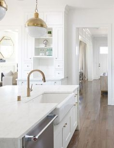 Brass Kitchen Faucet and farmhouse sink. I love how much warmth brass can bring to a white kitchen! White kitchen with brass lighting, brass faucet and brass hardware. #brass #kitchen #faucet #hardware #lighting #farmhousesink Ramage Company. Leslie Cotter Interiors, LLC