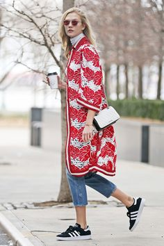 Karlie Kloss wears an oversize cardigan by Ermanno Scervino, cropped jeans, Adidas Gazelle sneakers, a white Miu Miu bag, and red sunglasses