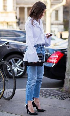 Look combinando calça jeans com barra assimétrica, camisa branca com manga em babados e scarpin.
