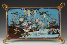 Japanese Style Tray attributed to Louis-Constant Sévin and Ferdinand Barbedienne, circa 1860 Rich landscape in cloisonné enamel on blue and brown background imitating Aventurine stone. The décor represents a river surrounded by wisterias, chrysanthemums, peonies, iris and reeds, led by birds and fishes. A frieze with floral pattern frames the set. The enamel rests on a beautiful bronze frame with four elephants heads feet topped by handles with typical lambrequin from Barbedienne's…