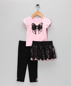 This set embellishes the basics with a sensational stretchy sequin-kissed lace skirt and accented bow top with puffed sleeves and a back button closure. For the girl who loves to layer, this set is perfect with the coordinating elastic-waistband leggings.Includes top, skirt and leggingsTop: 60% cotton / 40% polyesterLeg...