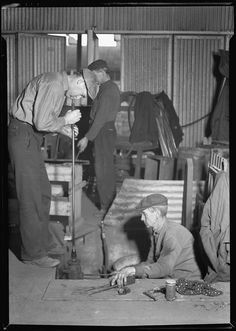 One man sitting while other man blows glass at a factory in Millville, New Jersey in 1936 (Lewis Hine).