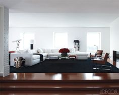 , a predominantly white living space sports a manly aesthetic. The black rug and accessories ground the extensive use of white and keep the room from looking pallid and boring. The scale of the furniture is man-sized, while the bold artwork and chrome accent pieces add to the masculine appeal. The fluffy black accent pillows, shag rug, and golden flowers soften the look without appearing feminine.