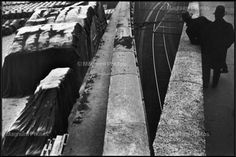 Henri Cartier-Bresson, France, 1932. /////////// Photograph /////////////  This photo has emphasized the lines going up on an angle, symbolizing movement. There is balance in the piece due to the large concrete lines dividing the picture in half. The large, black covered objects on one half and train tracks and men on the other add variety to the photograph as a whole. From the slight bird's eye view and the men hunched over the side, you can imagine a train about to come around the curve of