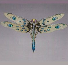 An Art Nouveau dragonfly brooch, by Louis Aucoc, French, circa 1900. Platinum, gold, enamel, diamond, emerald, ruby and horn. —
