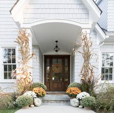Love this beautiful white home with a wood door and classic fall decorations