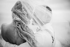 This photo is gorgeous. Bride and Groom behind the veil. | Photo by Eric Boneske