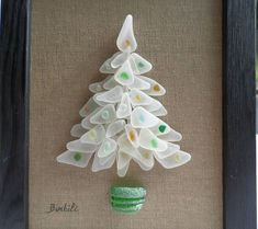 Seaglass Christmas tree, Christmas tree, white christmas decoration. White christmas tree and multicolored balls to match any interior! This Christmas tree is made of guenuine sea glass that I found on the beach at the edge of the Atlantic Ocean. It is presented in a black stained wood frame! Dimension:4.72 inches X 7.08 inches without frame 6.29 inches x 8.26 inches with the frame #seaglasscrafts