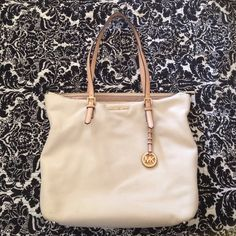 Authentic MK leather bag. This is a gorgeous large MK handbag with many pockets. It's soft cream leather & adorable buckle straps go with any outfit. This is one of my fav's, but I need to clean out my closet since I have too many handbags. There is a small smudge on the back that reflects price, otherwise it's in excellent condition. MICHAEL Michael Kors Bags Shoulder Bags