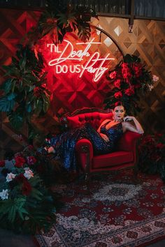 'Til Death Do Us Party neon sign for modern wedding backdrop with tropical plants, roses and red lounge. Bride wearing glamorous navy sequin dress | White Fox Studios