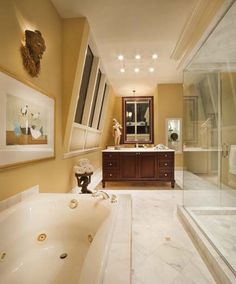 A large master bathroom remodel required a creative floor plan. Therefore a back-to-back double sink vanity was designed to float in the room with a mirror suspended from the ceiling. Photo by George Dzahristos. Paul Feiten Design Paul Feiten - Bloomfield Hills, M