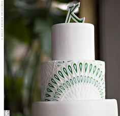 "Megann wanted the cake to be simple and chic and be true to their theme -- the three-tiered white and green cake mimicked the design of the programs and was topped with a ""K."""