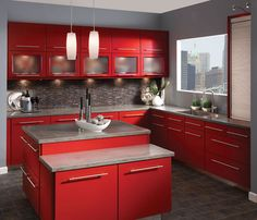 Vibrant cooking space. Red shines bright and bold in this sleek kitchen and is balanced by the texture and tone of beautiful slate gray countertops and tile backsplash. Beautiful brushed nickel pulls that are long and line compliment the lines of the cabinetry and are a clean finish to the high-gloss doors. When using color in a kitchen, make sure to include a natural resting space for the eye by balancing a hue with a neutral tone on a wall, counter or floor.