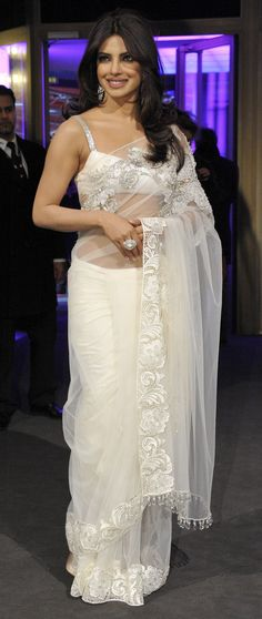 Priyanka Chopra sari is always as dashing and sensational as she herself is. In the above picture, the sari worn by Priyanka is embellished with beautiful embroidery, the border is done in velvet material. The blouse of the saree is also matching silk material as the saree itself. The blouse has been made as shorter as it could have been. There is a beautiful silver embroidery on the straps of the sari. The elegant net saree dazzles its way through evening parties especially receptions