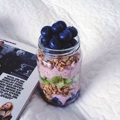 granola and berry yogurt with kiwi and blueberries.