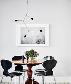 Simple dining room with a modern chandelier and black and white photography