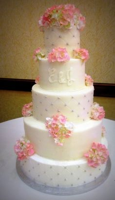 White wedding cake with bling accents and pink flowers
