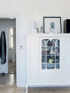 Det gamle skab er et arvestykke, som Charlotte har malet hvidt. Det gemmer på glas, porcelæn, bøger, spil og ting i farver, der ikke passer til den øvrige indretning. Det sort/ hvide billede er af Victor Flyvbjerg.