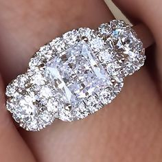 This is my engagement ring but the center diamond is round 2.5K. Then I have two wedding bands. 1 on each side 5 round stones to guard the engagement ring = 1k each ring settings are 14 caret white gold.
