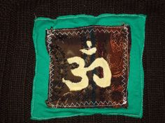 Jersey-knit Om symbol on brocade, attached to sweater back