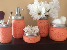 Paint mason jars a rustic red color for the flowers, soap dispenser, q tips, tooth brushes, makeup, etc.