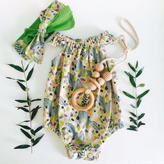 Glorious #flatlay by @bebe_evie_louise featuring our personalised organic teething necklace and gorgeous romper and head wrap by @rubyowl_babywear  #nocnoc #woodentoys #teethingnecklace #handmadewithlove #shopsmall #babylay #love