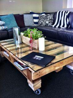 Une table basse palette avec plateau en verre transparent et espaces de rangement