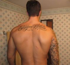 A set of two huge words covering the upper part of the back. These words are written in a stylish slanting font. The art used to extend some letters up or downwards make the tattoo cool.