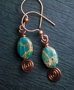 Aqua Terra ~ Earth and ocean mingle in these lovely natural gemstone earrings. In these the Aqua Terra Jasper oval beads are wirewrapped onto handcrafted copper ear wires with a pretty spiral end detail. These earthy little beauties will warm and brighten your day and polish off that perfect look. ~ Genuine 10x14mm Green Aqua Terra smooth oval gemstone beads. ~ Handcrafted copper spiral ear wires. ~ Earrings measure approx. 2 inches (51mm) in length. Comes wrapped in an elegant mossy ...