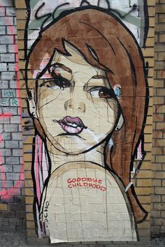 Graffiti artist El Bocho reflects the feeling of growing up in this paste up street art of a pretty girl looking over her shoulder