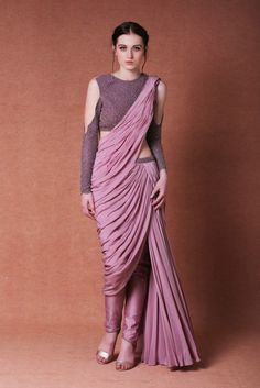 Featuring a lilac saree inspired drape ensemble done in crepe base along with attached chanderi pants and embroidered waist band. Blouse of the outfit comes with a sheer net back and front & sleeves are intricately embroidered with resham, bugle beads, and pearl beads. Color: Purple Material: Crepe and Chanderi Dry clean only
