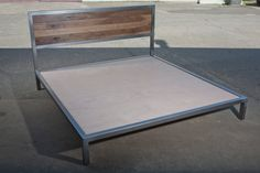 This is a king sized platform bed made of tube steel with inlay walnut headboard pieces. The walnut is finished in a clear matte finish and the metal