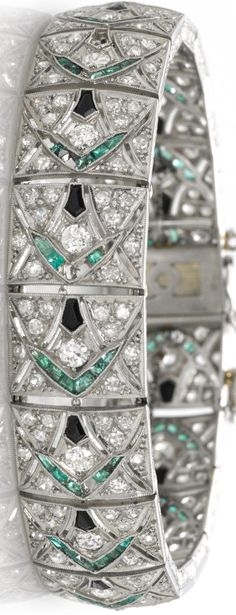 An art deco diamond, emerald and black onyx bracelet, circa 1925.   estimated total diamond weight: 3.40 carats; gross weight approximately: 44.6 grams; mounted in platinum and eighteen karat white gold; length: 7in.