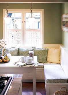 A snug and comfy banquette in a pretty green kitchen.