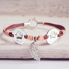 Custom leather bracelet with two actual pawprints and angel wing. . . . #customjewelry #leatherbracelet #leather #petlovers #personalized #gifts #giftideas #giftsforher #doglovers #catlovers #bracelet