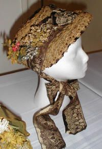"""ca. 1880–1883 Fancy straw """"poke-style"""" bonnet with original trims.    It features a nosegay of naturalistic field flowers and Jacquard woven silk ribbon that resembles lace overlay.  The interior is lined with a pleating of harmonizing brown fabric."""